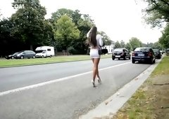 Gorgeous brunette shows off her legs on the street